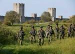 Les soldats du régiment blindé de Skaraborg de l'armée suédoise patrouillent devant le mur de la ville de Visby lors d'une manoeuvre militaire sur l'île de Gotland, le 14 septembre 2016. (Crédits : Soren Andersson, EPA)