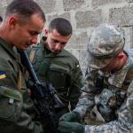 Un sous officier de la 173rd Airborne Brigade américaine instruit un soldat ukrainien sur le maniement du M4 pendant l'exercice Rapid Trident.