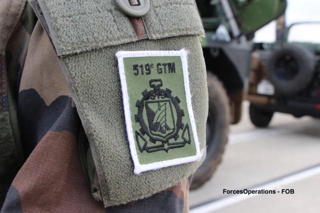L'insigne du 519e GTM, une roue crénelée de 12 pièces ajourée, symbole des unités du Train, supportant un sampan indochinois qui évoque le lieu de création et d'emploi initial de l'unit, ainsi que la mission de transport