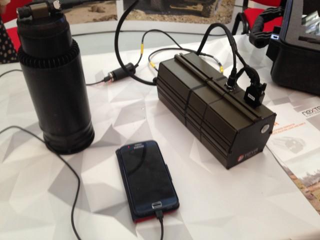 """Le """"thermos"""" sur la gauche fournit l'énergie pour le générateur sur la droite qui charge le téléphone portable en face (Crédit photo: Christina Mackenzie)"""
