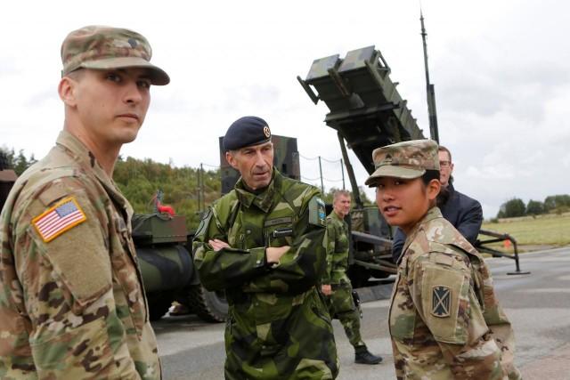 Micael Byden, commandant en chef des forces armées suédoises, s'entretient avec deux soldats américains lors de l'exercice militaire suédois «Aurora 17» sur l'aérodrome de Save à Goteborg, en Suède, le 13 septembre 2017. Derrière eux, le système anti-missiles américain Patriot commandé par Stockholm au grand dam des missiliers européens (Crédits : Reuters)