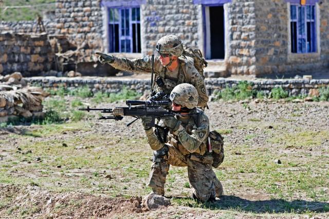 Cpl. Brian Lewis signale un emplacement possible de l'ennemi au Pfc. Josh Ball lors d'une patrouille à pied à Shaway Valley dans la province afghane de Khowst, le 2 juin 2012.   (Photo de l'US Army par le Sgt Staff. Jason Epperson)